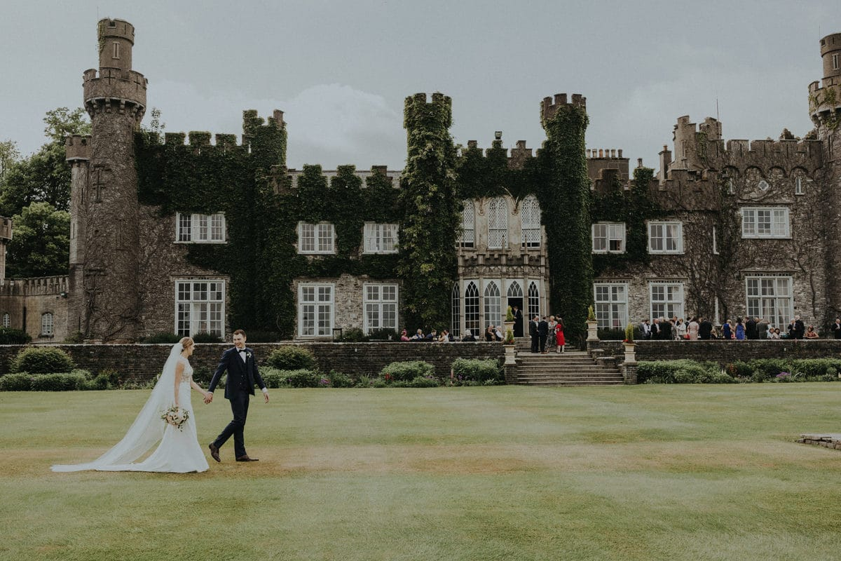 Real Weddings | Vinka Design | Real Brides Wearing Vinka Gowns | Paige and Ciaran walk along outside Irish Castle with dress showing off length and train