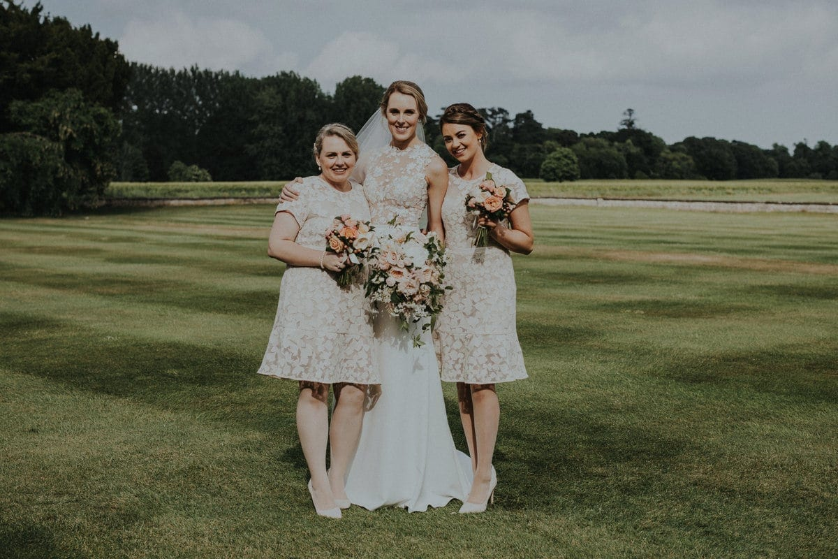 Real Weddings | Vinka Design | Real Brides Wearing Vinka Gowns | Paige and Ciaran bride and bridesmaids on green