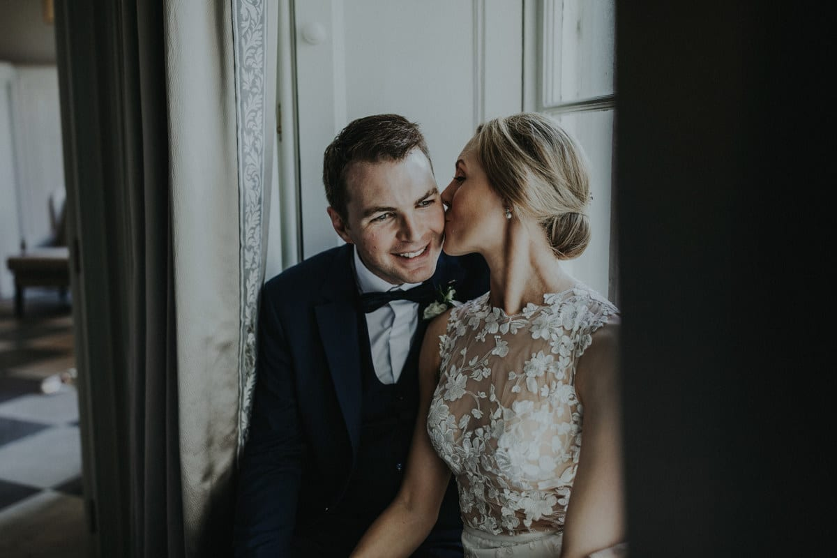 Real Weddings | Vinka Design | Real Brides Wearing Vinka Gowns | Paige and Ciaran kiss seated with lace bodice detail highlighted