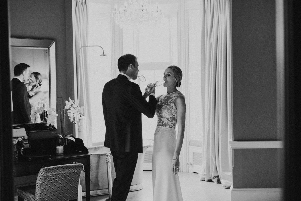 Real Weddings | Vinka Design | Real Brides Wearing Vinka Gowns | Paige and Ciaran drink champagne with linked arms lace bodice detail highlighted in black and white