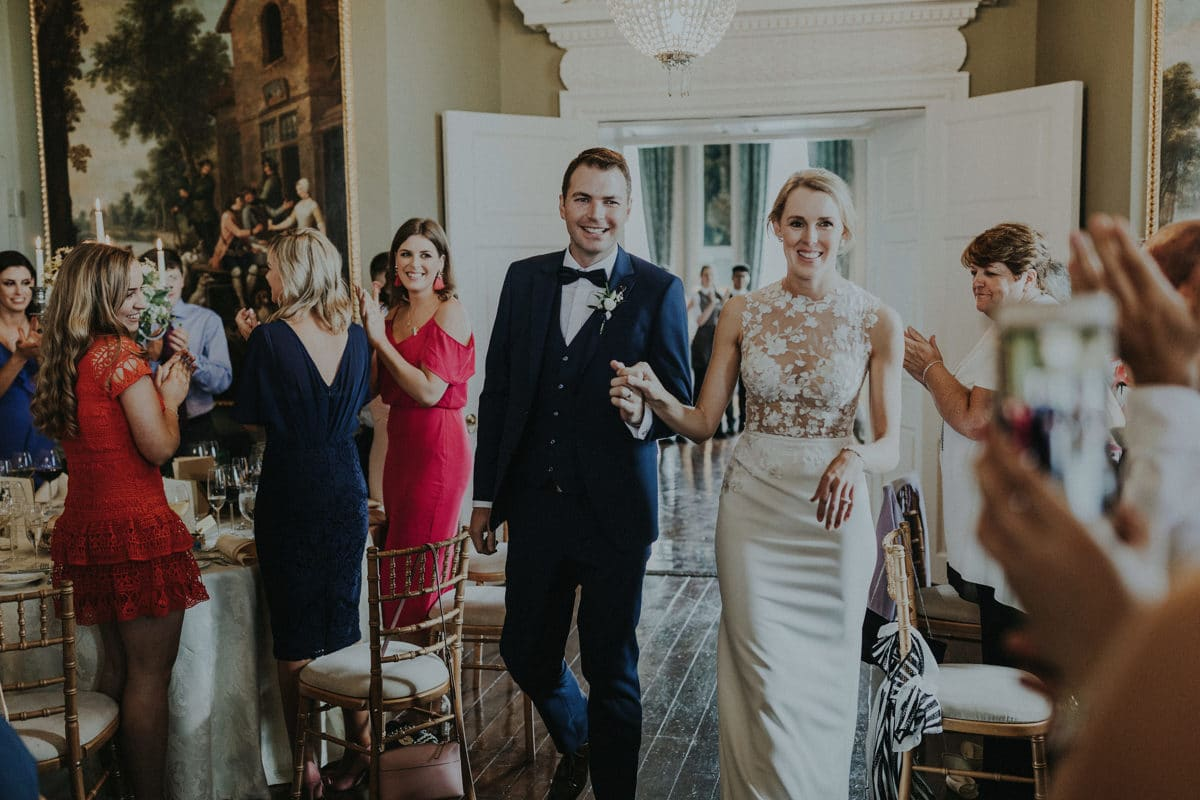 Real Weddings | Vinka Design | Real Brides Wearing Vinka Gowns | Paige and Ciaran arrive at reception stunning bespoke gown detail of sheer front with lace embellishments showing