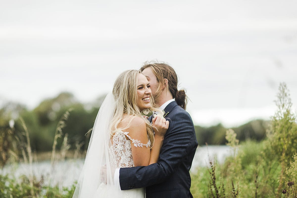 Real Weddings | Vinka Design | Real Brides Wearing Vinka Gowns | Olivia and Brayden lying in field laughing close up with off the shoulder dress detail showing