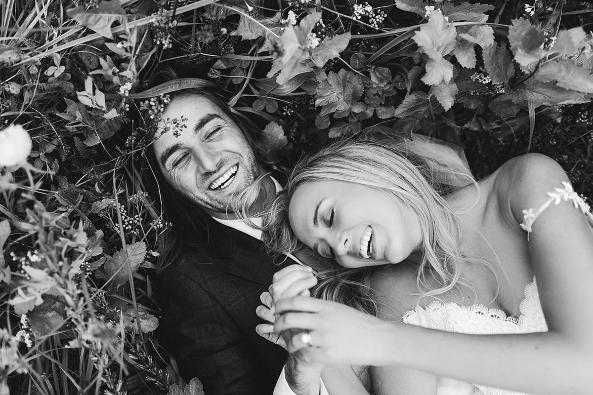 Real Weddings | Vinka Design | Real Brides Wearing Vinka Gowns | Olivia and Brayden lying in field laughing close up in black and white