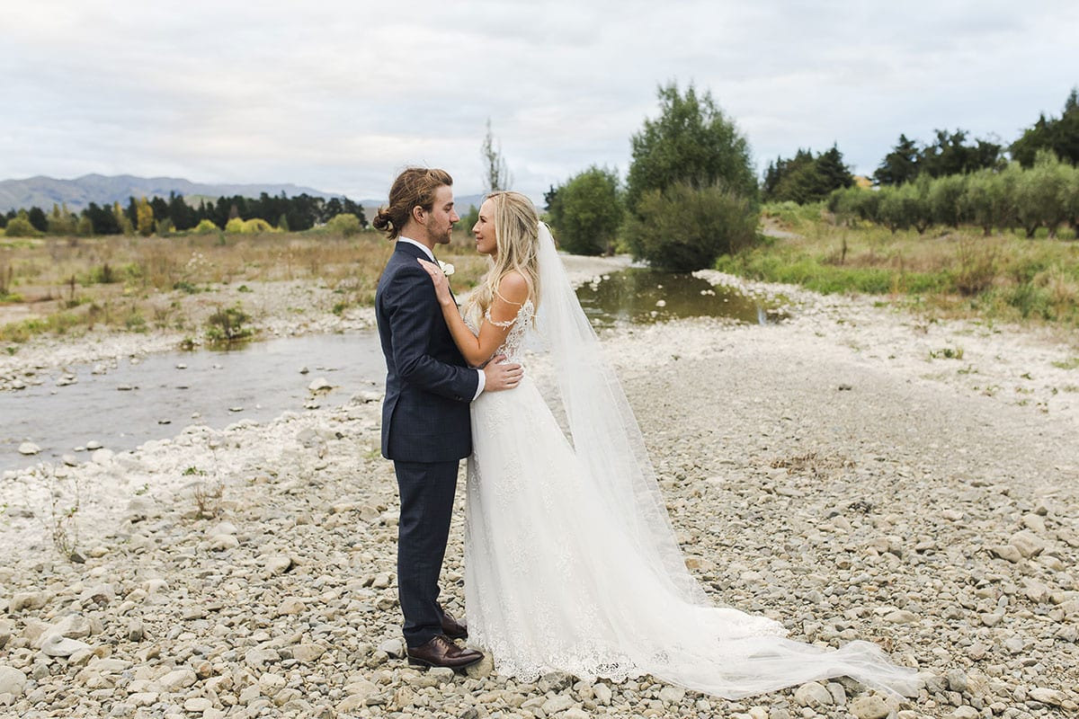 Real Weddings | Vinka Design | Real Brides Wearing Vinka Gowns | Olivia and Brayden in river bed with beautiful bespoke floaty layers of dress and train on ground
