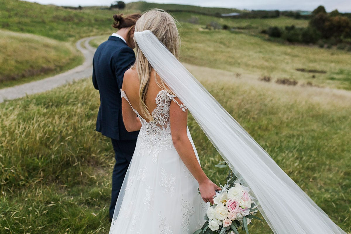 Real Weddings | Vinka Design | Real Brides Wearing Vinka Gowns | Olivia and Brayden in field with veil in wind and beautiful bespoke dress lace detail of low back
