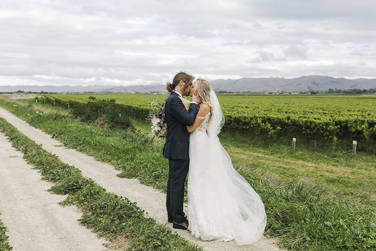 Real Weddings | Vinka Design | Real Brides Wearing Vinka Gowns | Olivia and Brayden kissing at vineyard