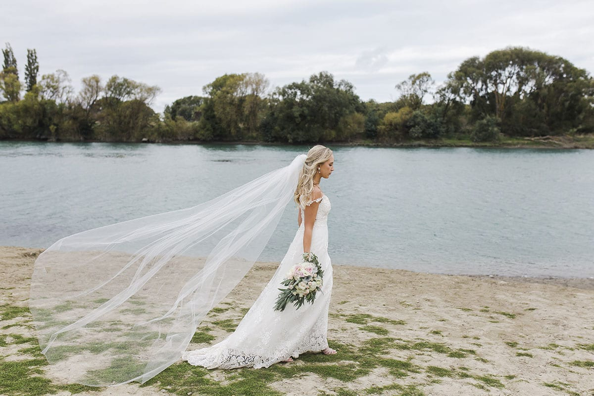 Real Weddings | Vinka Design | Real Brides Wearing Vinka Gowns | Olivia and Brayden - Olivia next to river with veil blowing in the breeze