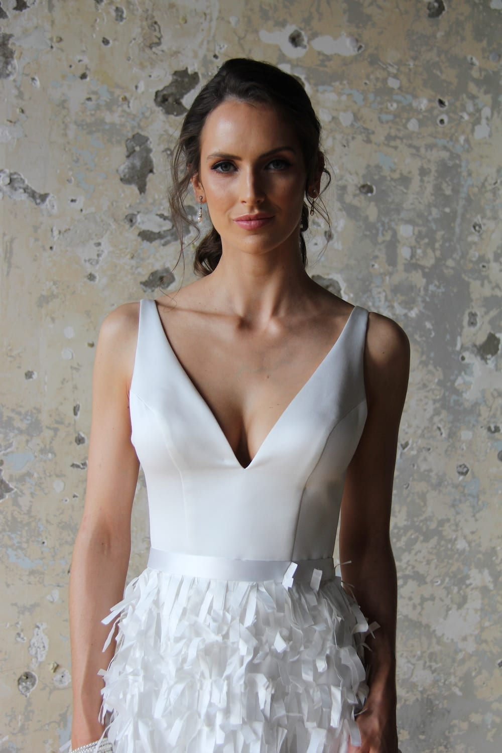 Female model wearing Vinka Design Modern Muse Wedding Dress. In chic warehouse the front detail of a gown with a deep v-neckline and a squared low back with a cut ribboned satin skirt.