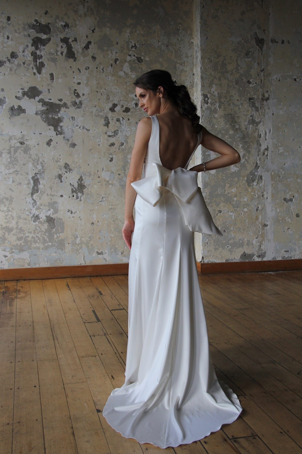 Female model wearing Vinka Design Modern Muse Wedding Dress. In chic warehouse the back detail of a gown with a bateau neckline and low scooped back gently flaring to a simple train with a detachable bow.