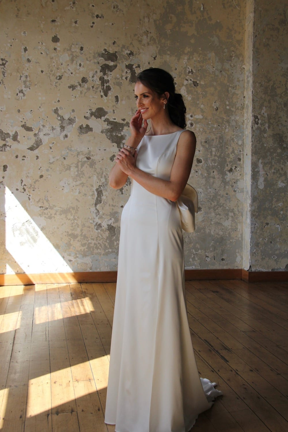 Female model wearing Vinka Design Modern Muse Wedding Dress. In chic warehouse the front detail of a gown with a bateau neckline and low scooped back gently flaring to a simple train with a detachable bow.