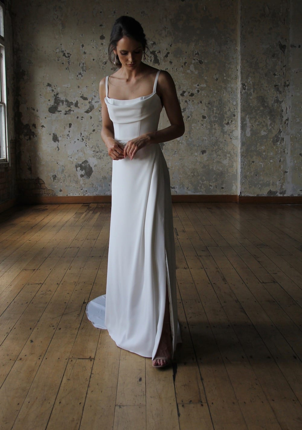 Female model wearing Vinka Design Modern Muse Wedding Dress. In chic warehouse the front detail of a gown of soft bridal crepe with a fitted bodice with soft draping over the bust line and a side split skirt.