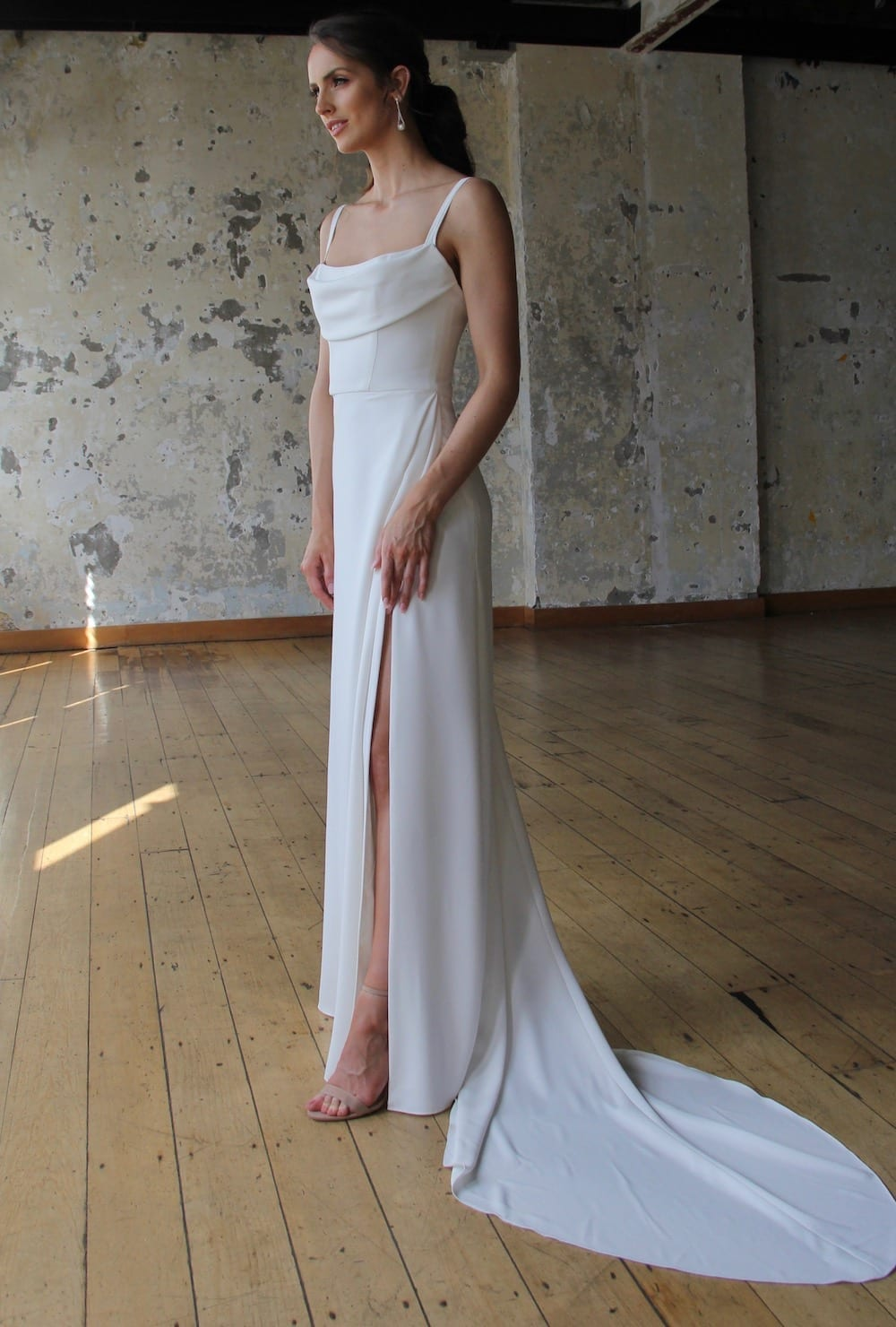 Female model wearing Vinka Design Modern Muse Wedding Dress. In chic warehouse the side detail of a gown of soft bridal crepe with a fitted bodice with soft draping over the bust line and a side split skirt.