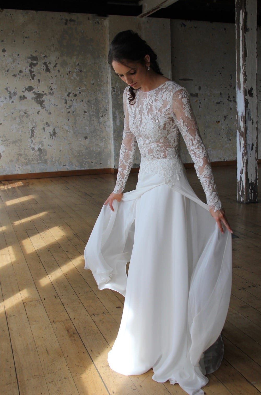 Female model wearing Vinka Design Modern Muse Wedding Dress. In chic warehouse the front detail of a gown with a high neckline and low back in silver-edged ivory lace, silk chiffon over viscose skirt with a train.