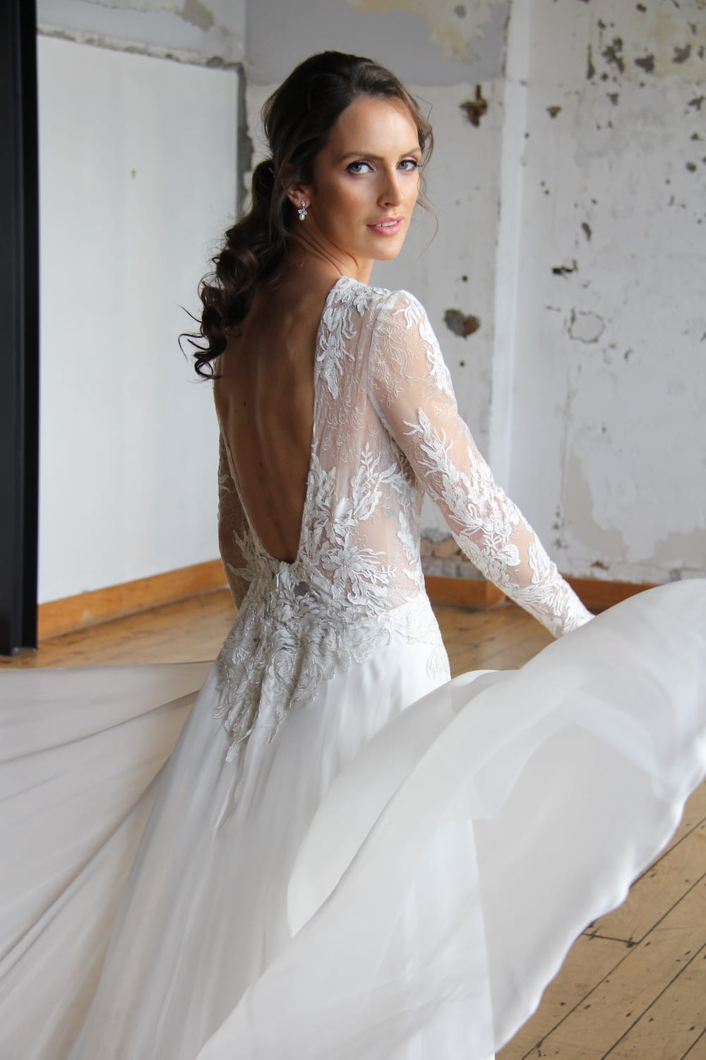 Female model wearing Vinka Design Modern Muse Wedding Dress. In chic warehouse the back detail of a gown with a high neckline and low back in silver-edged ivory lace, silk chiffon over viscose skirt with a train.