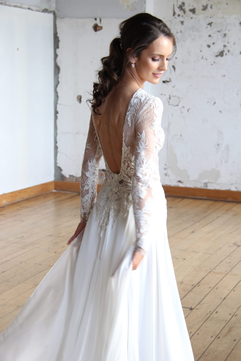 Female model wearing Vinka Design Modern Muse Wedding Dress. In chic warehouse the side detail of a gown with a high neckline and low back in silver-edged ivory lace, silk chiffon over viscose skirt with a train.