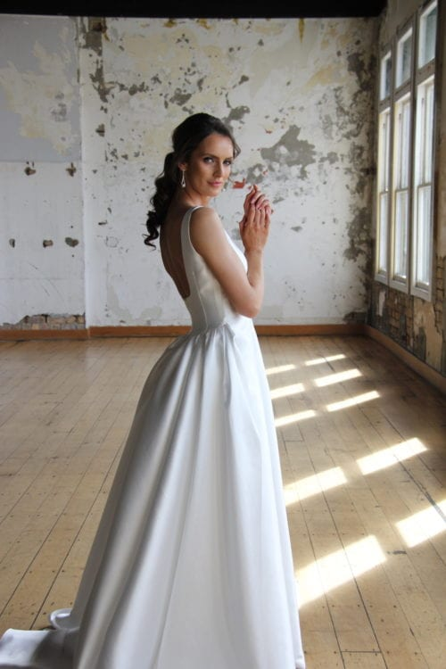 Female model wearing Vinka Design Modern Muse Wedding Dress. In chic warehouse the side detail of a gown with a full skirt and fitted bodice, deep scoop neckline and cinched waist.