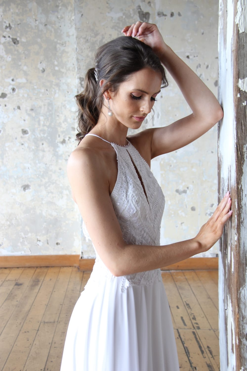 Female model wearing Vinka Design Modern Muse Wedding Dress. In chic warehouse the side detail of a light, halter-necked gown with a fluid chiffon skirt.