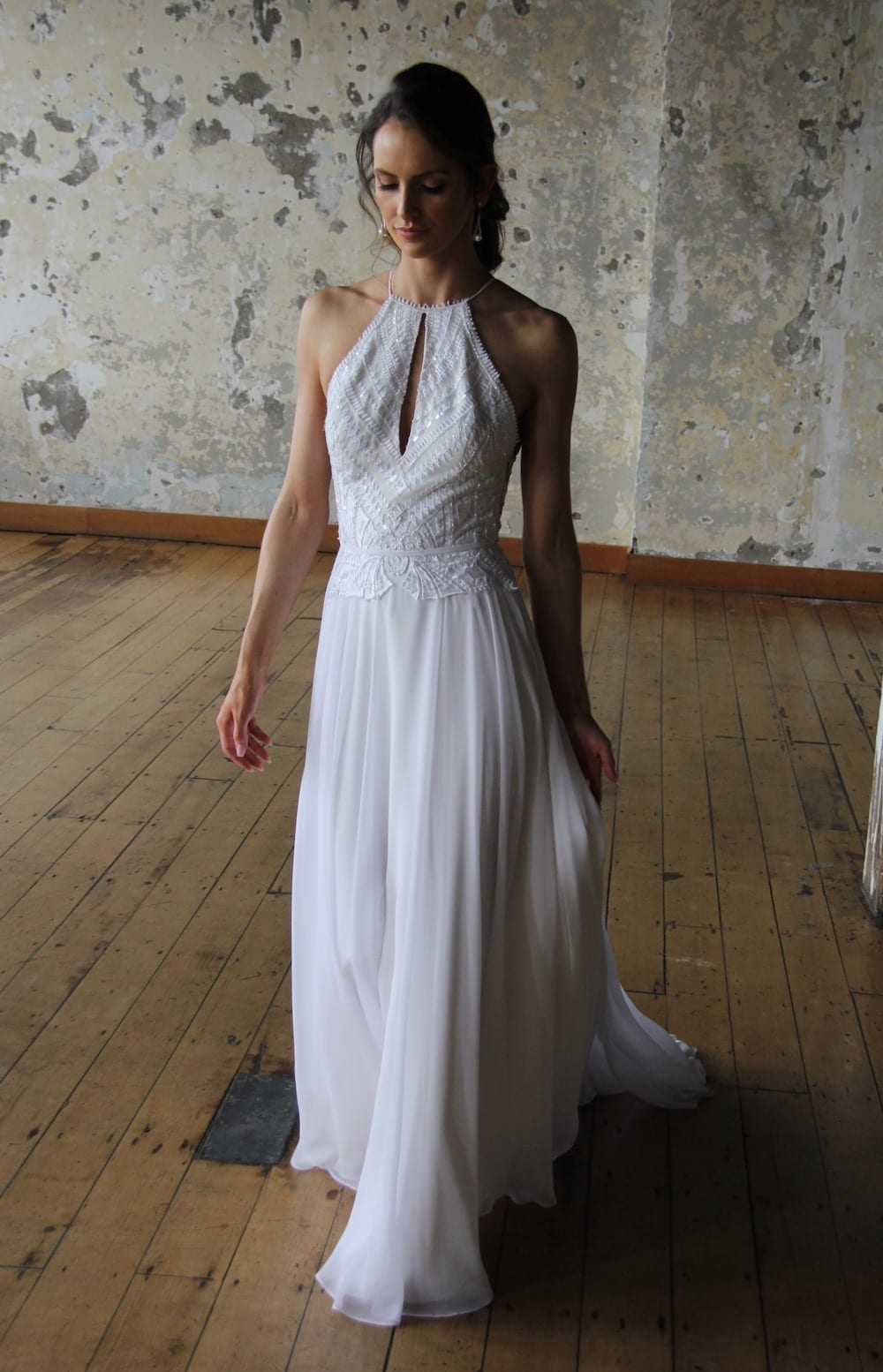 Female model wearing Vinka Design Modern Muse Wedding Dress. In chic warehouse the front detail of a light, halter-necked gown with a fluid chiffon skirt.