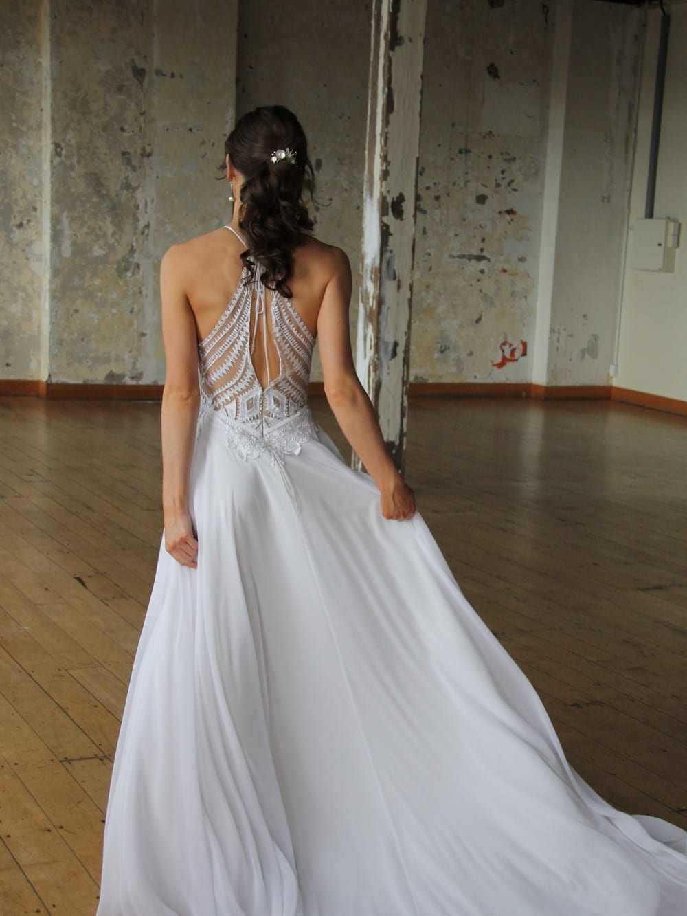 Female model wearing Vinka Design Modern Muse Wedding Dress. In chic warehouse the back detail of a light, halter-necked gown with a fluid chiffon skirt.