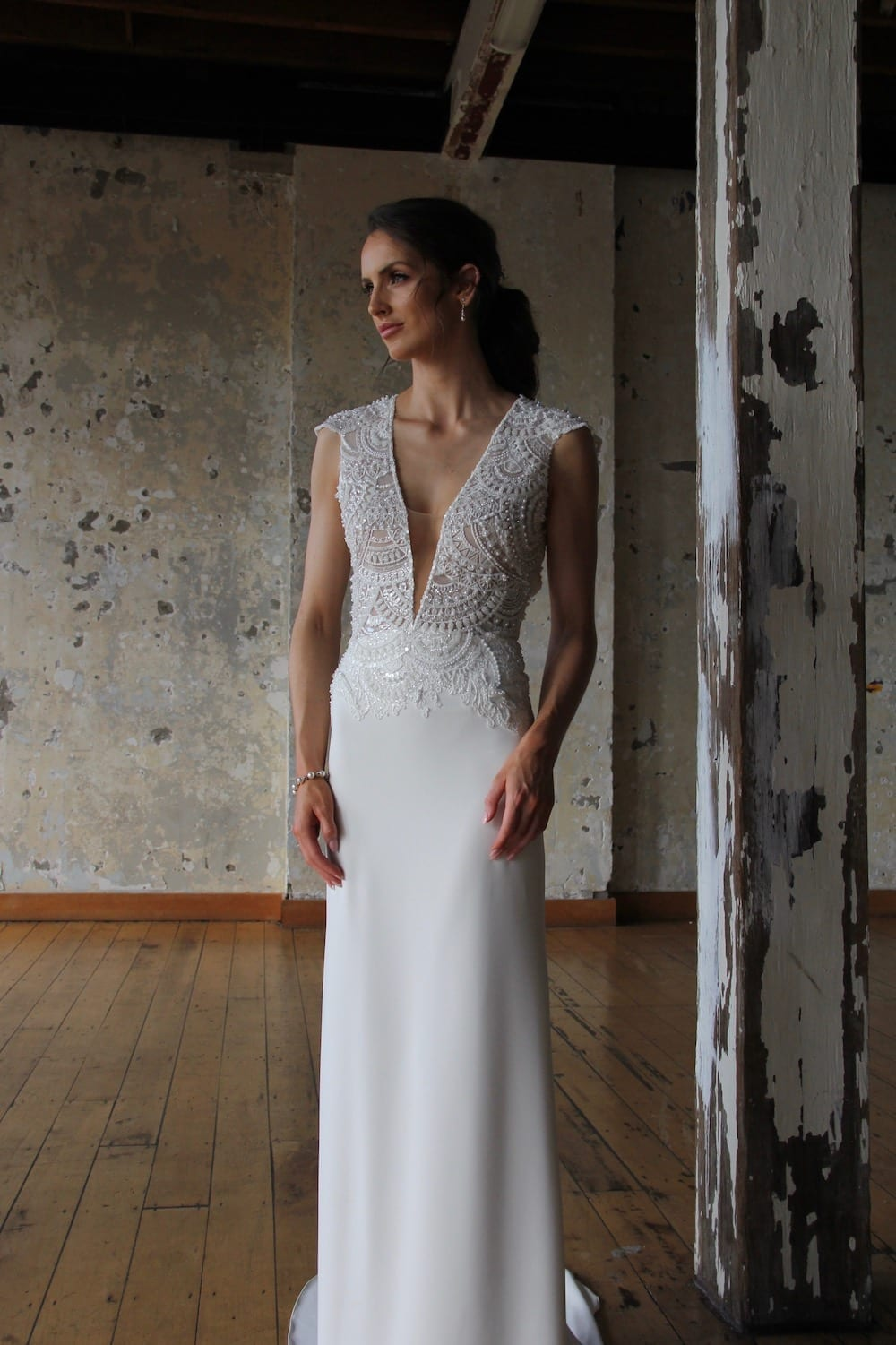 Female model wearing Vinka Design Modern Muse Wedding Dress. In chic warehouse the front detail of a gown with a a richly beaded lace bodice, deep v-neckline, wide shoulders and a slim crepe skirt with a train.