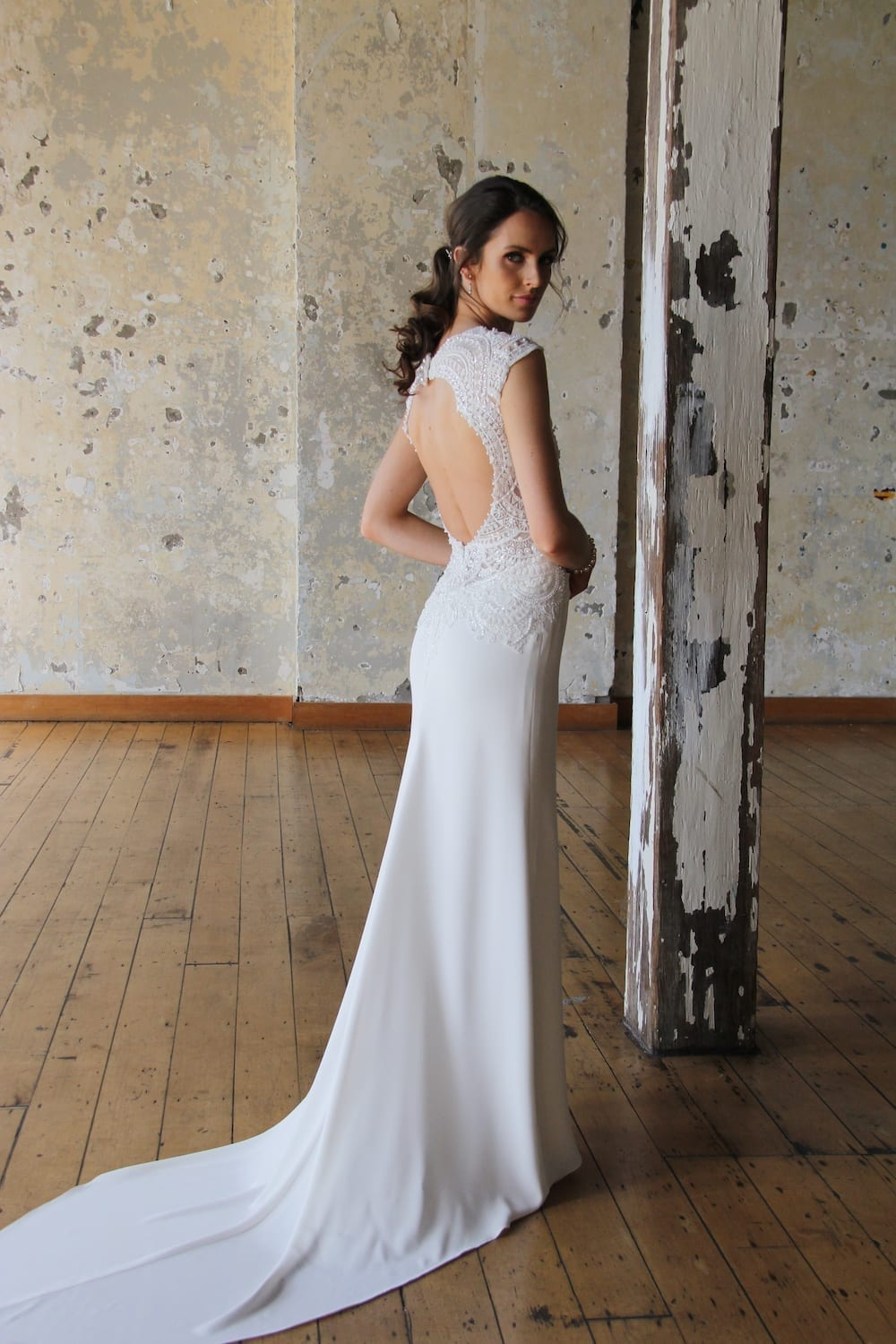Female model wearing Vinka Design Modern Muse Wedding Dress. In chic warehouse the back detail of a gown with a a richly beaded lace bodice, deep v-neckline, wide shoulders and a slim crepe skirt with a train.