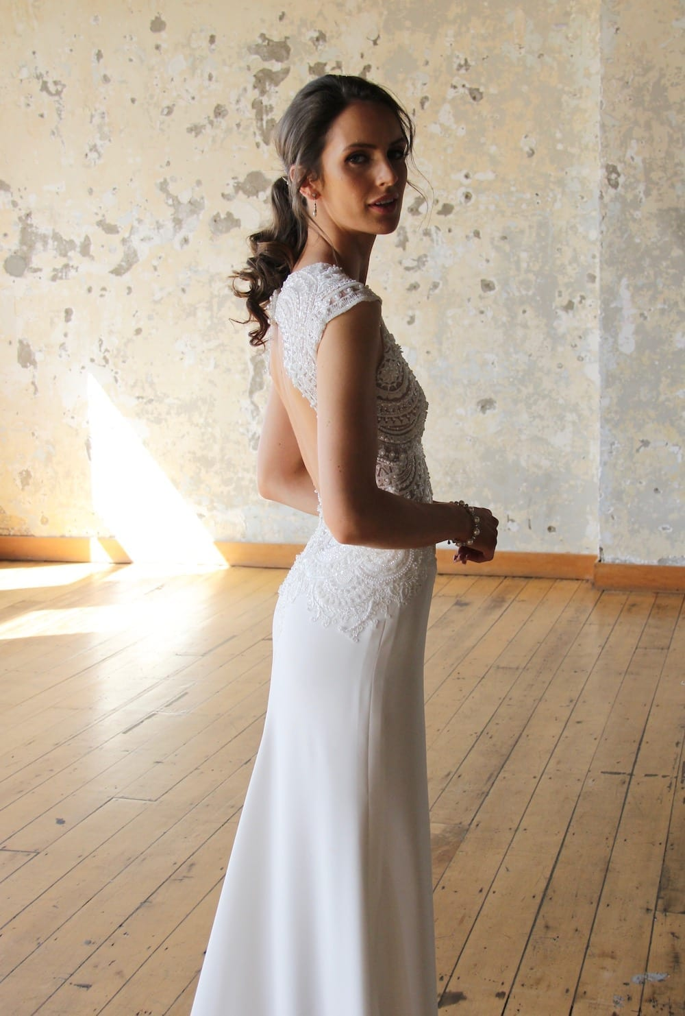 Female model wearing Vinka Design Modern Muse Wedding Dress. In chic warehouse the side detail of a gown with a a richly beaded lace bodice, deep v-neckline, wide shoulders and a slim crepe skirt with a train.