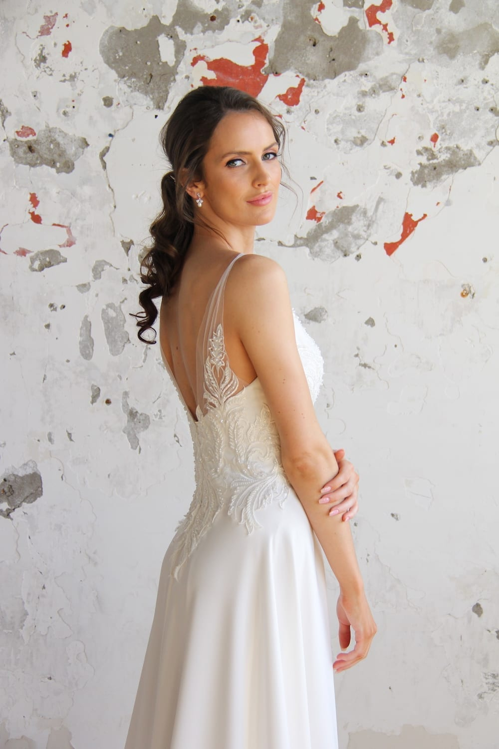 Female model wearing Vinka Design Modern Muse Wedding Dress. In chic warehouse the side detail of a gown with beaded lace and tulle bodice and bridal crepe skirt with train.