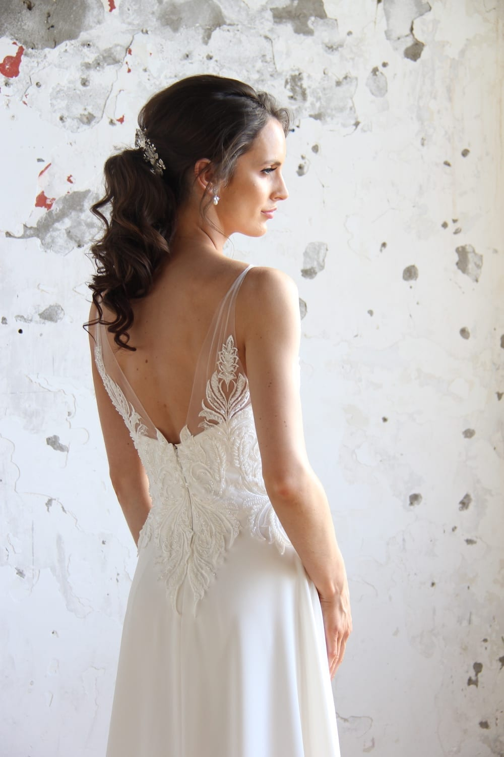 Female model wearing Vinka Design Modern Muse Wedding Dress. In chic warehouse the back detail of a gown with beaded lace and tulle bodice and bridal crepe skirt with train.