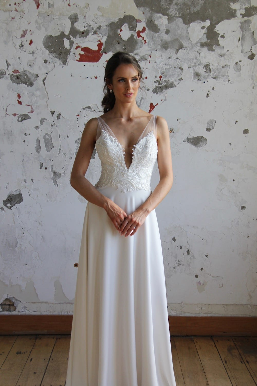 Female model wearing Vinka Design Modern Muse Wedding Dress. In chic warehouse the front detail of a gown with beaded lace and tulle bodice and bridal crepe skirt with train.