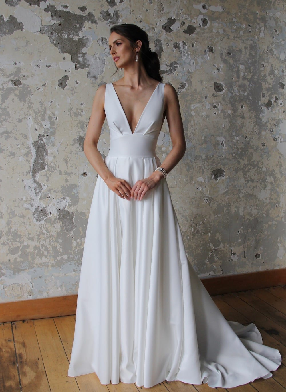 Female model wearing Vinka Design Modern Muse Wedding Dress. In chic warehouse the front detail of a gown with plunging v-neckline, Clean, sharp lines and skirt with deep pleated folds and pockets.
