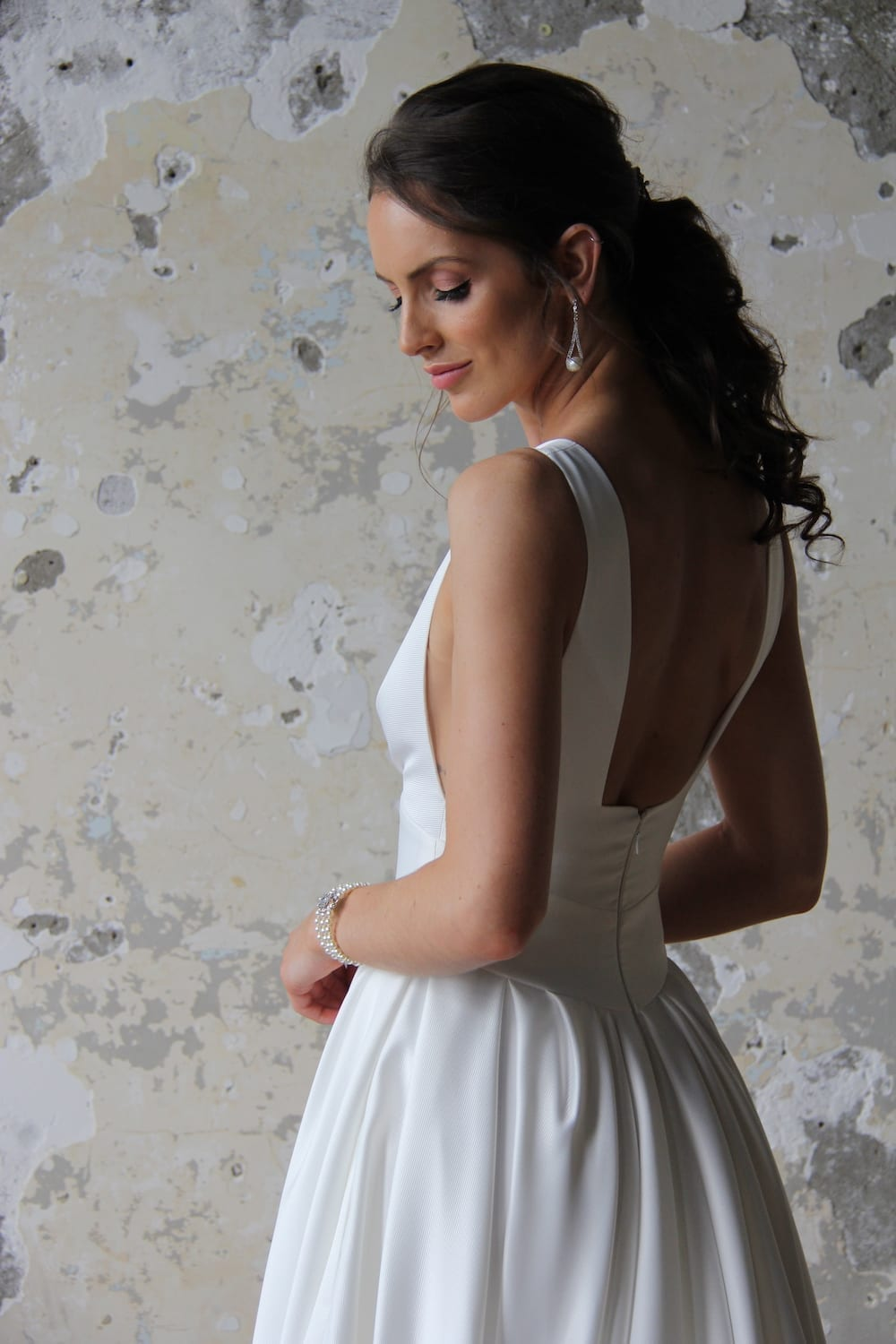 Female model wearing Vinka Design Modern Muse Wedding Dress. In chic warehouse the back detail of a gown with plunging v-neckline, Clean, sharp lines and skirt with deep pleated folds and pockets.