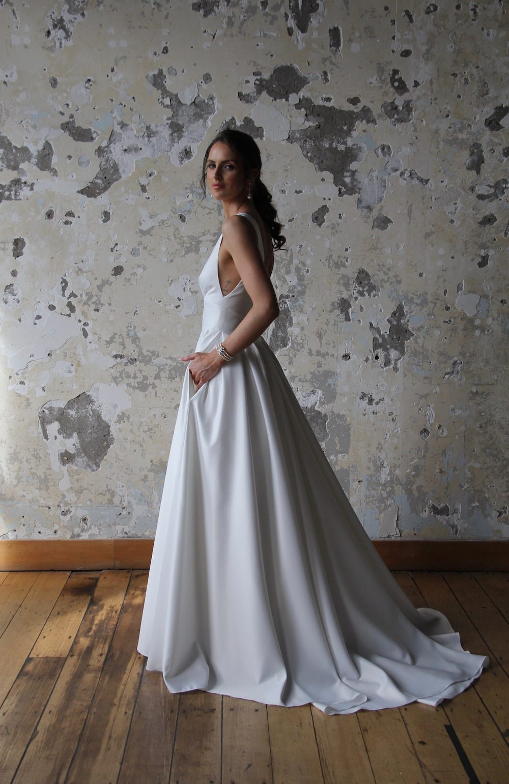 Female model wearing Vinka Design Modern Muse Wedding Dress. In chic warehouse the side detail of a gown with plunging v-neckline, Clean, sharp lines and skirt with deep pleated folds and pockets.