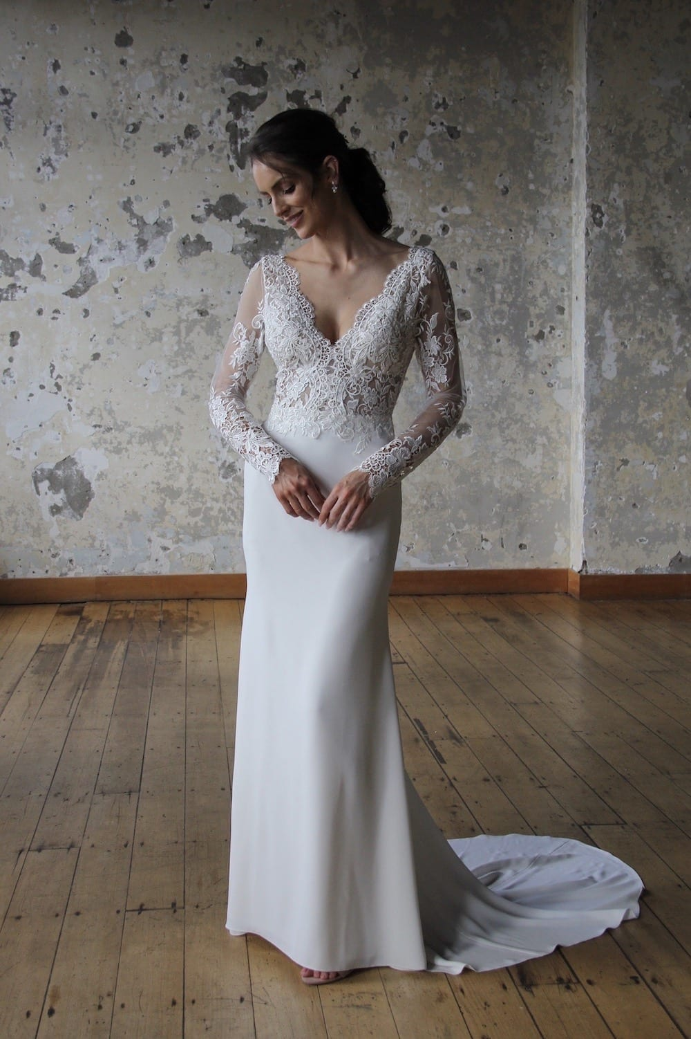 Female model wearing Vinka Design Modern Muse Wedding Dress. In chic warehouse the front detail of a gown with v-neckline, intricate bodice, long lace sleeves, and Bridal crepe skirt.