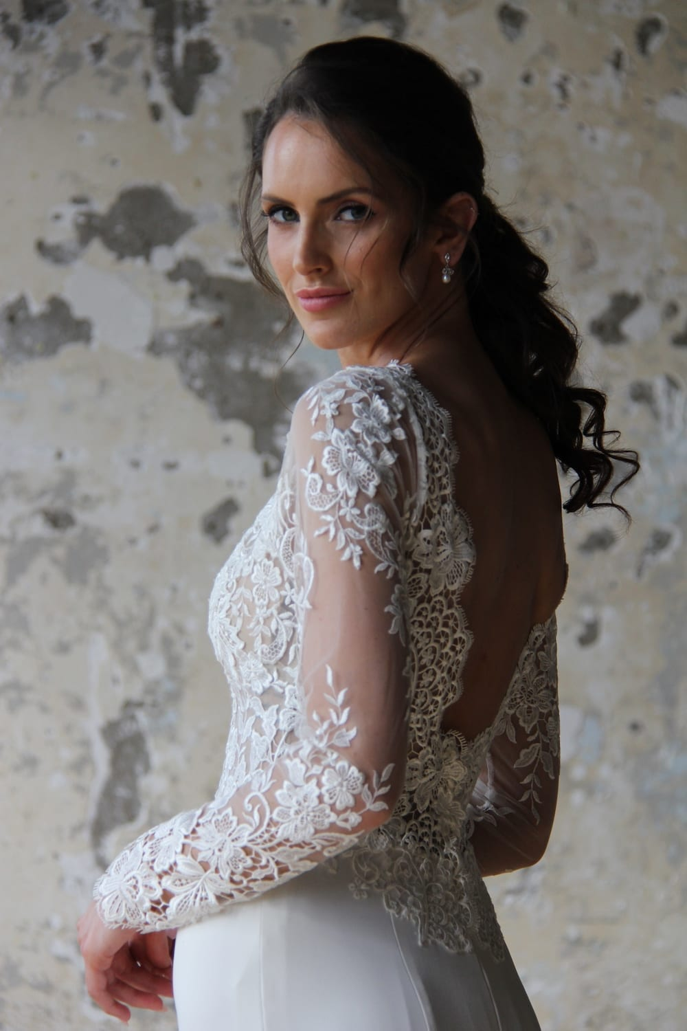 Female model wearing Vinka Design Modern Muse Wedding Dress. In chic warehouse the side detail of a gown with v-neckline, intricate bodice, long lace sleeves, and Bridal crepe skirt.
