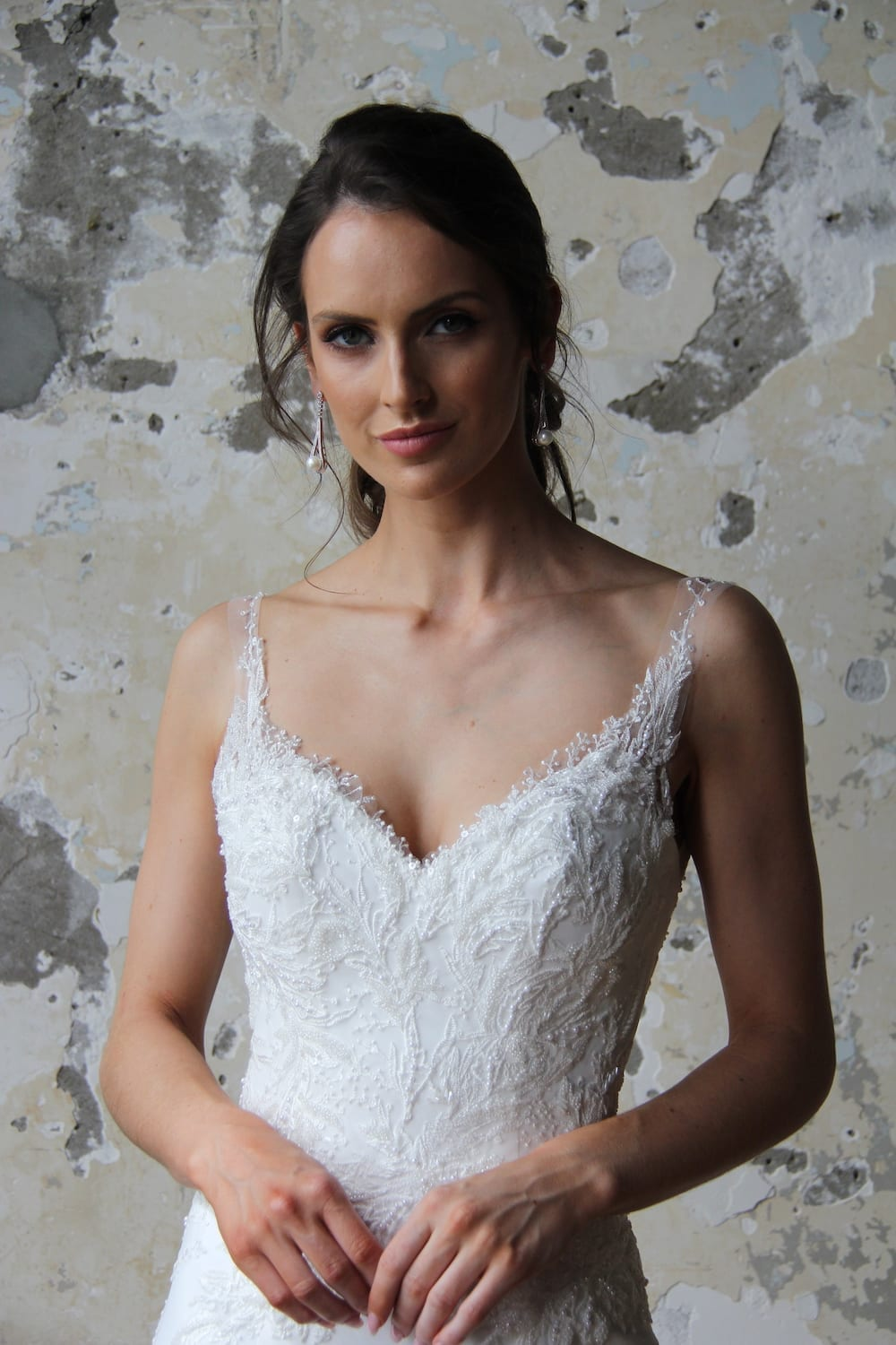 Female model wearing Vinka Design Modern Muse Wedding Dress. In chic warehouse the front detail of a gown with delicate beaded leaf lace, sheer back straps and bridal crepe skirt with train.