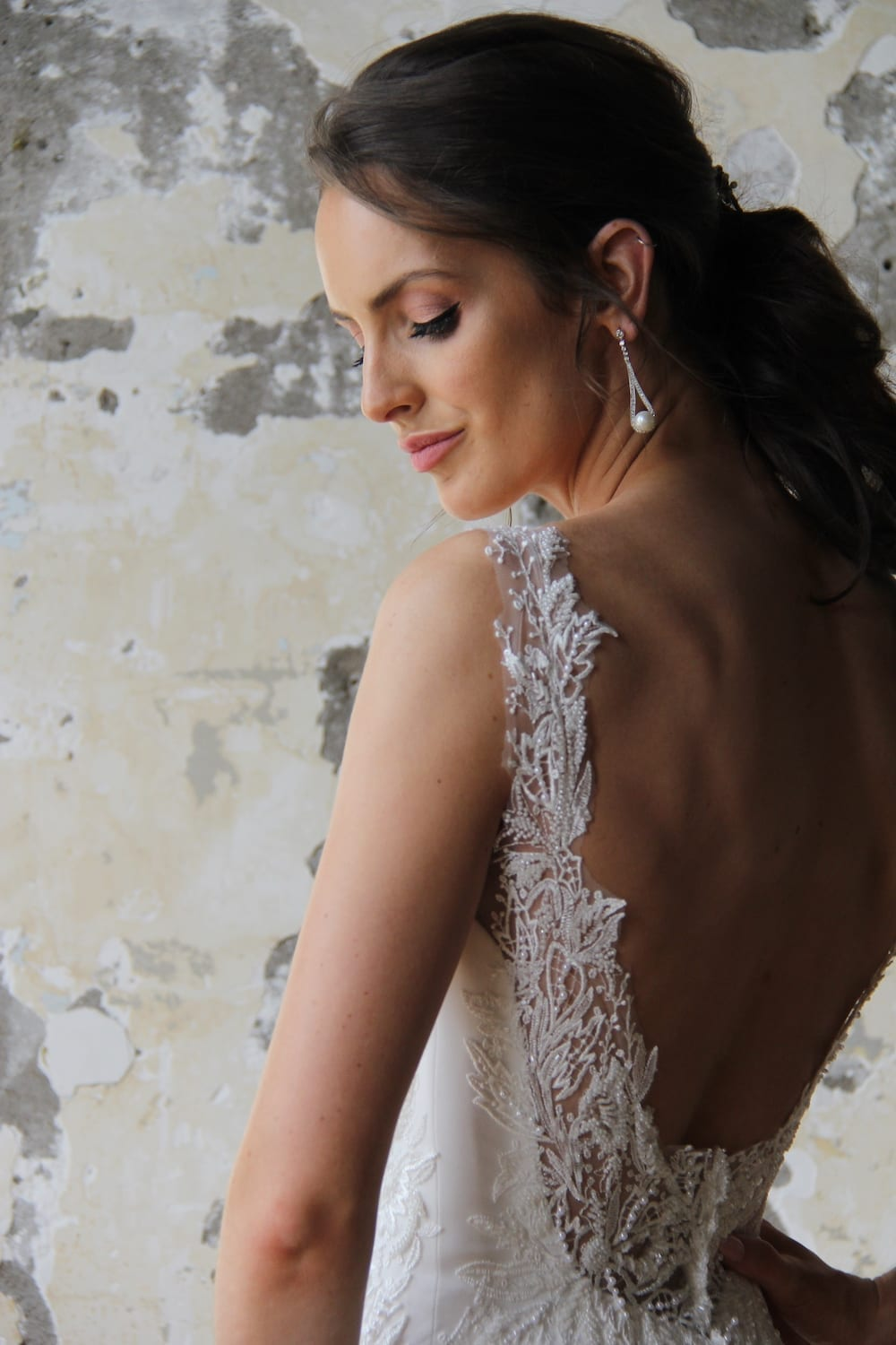 Female model wearing Vinka Design Modern Muse Wedding Dress. In chic warehouse the back detail of a gown with delicate beaded leaf lace, sheer back straps and bridal crepe skirt with train.