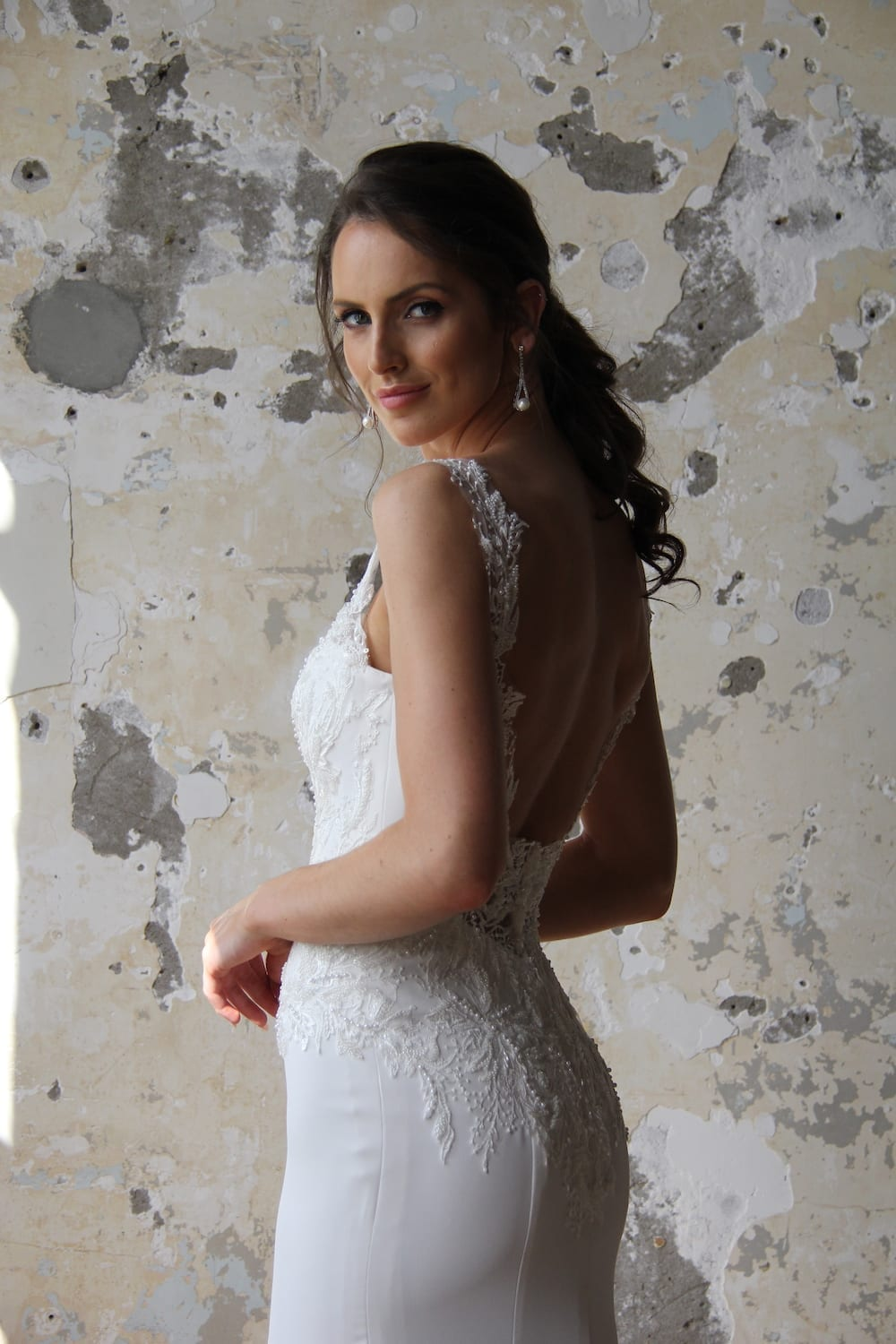 Female model wearing Vinka Design Modern Muse Wedding Dress. In chic warehouse the side detail of a gown with delicate beaded leaf lace, sheer back straps and bridal crepe skirt with train.