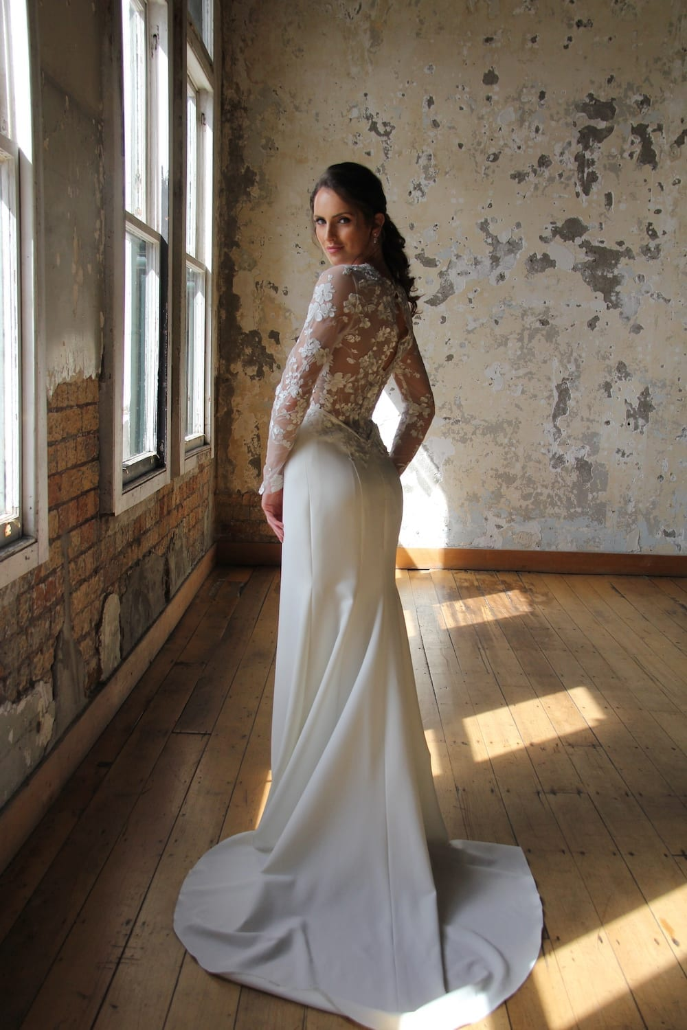 Female model wearing Vinka Design Modern Muse Wedding Dress. In chic warehouse the back detail of a gown with Long slender lace sleeves and a high neck subtle silver thread mixed in with ivory tones down into the stretch skirt.