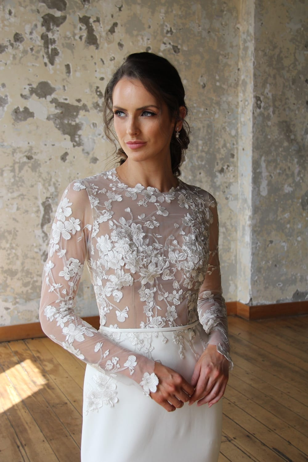 Female model wearing Vinka Design Modern Muse Wedding Dress. In chic warehouse the front detail of a gown with Long slender lace sleeves and a high neck subtle silver thread mixed in with ivory tones down into the stretch skirt.