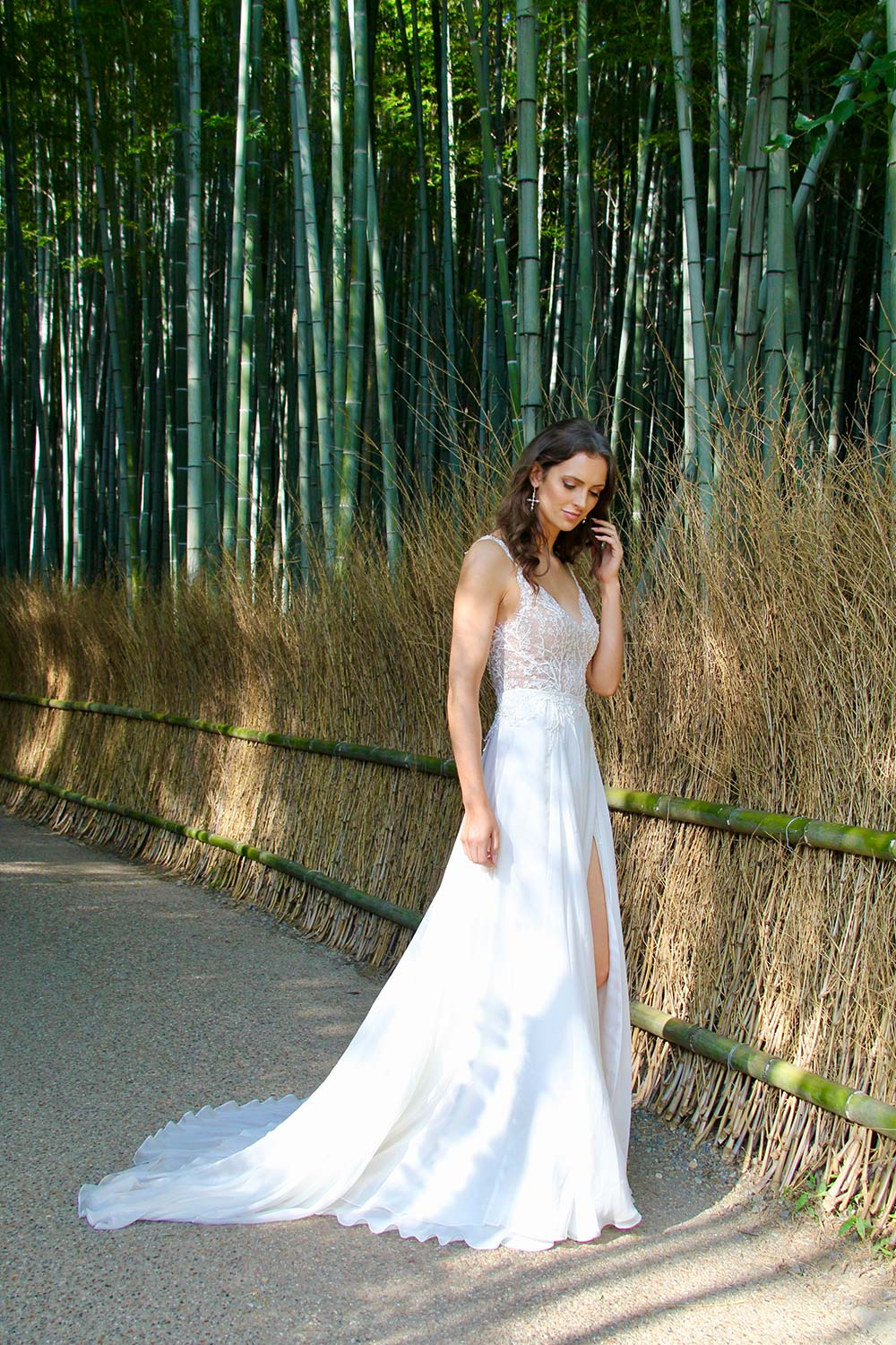 Female model wearing Vinka Design An Oriental Affair Wedding Dress. In a Japanese bamboo forest the front detail of a gown with a bodice of two beaded laces on a nude base and a silk chiffon skirt with side split.