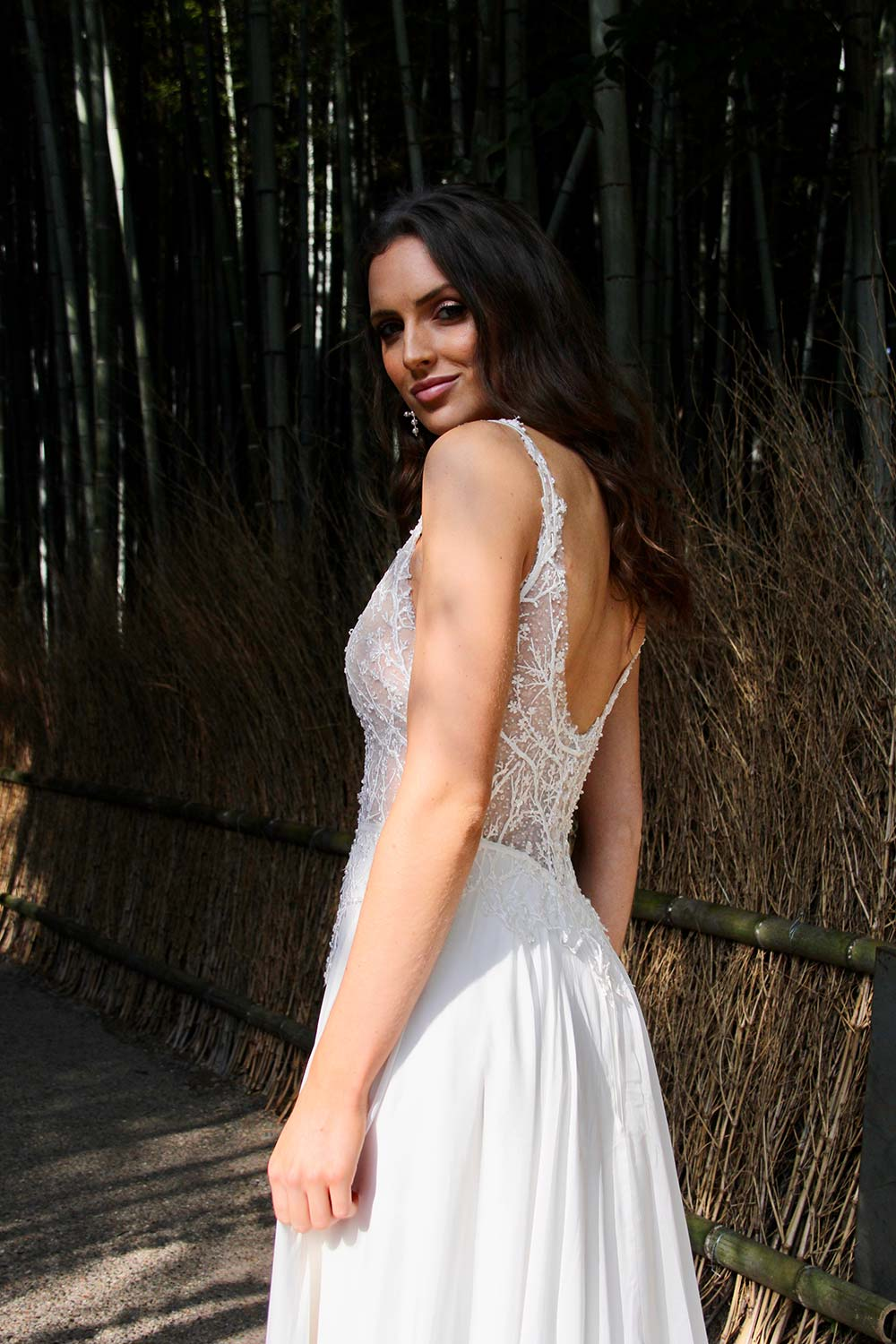 Female model wearing Vinka Design An Oriental Affair Wedding Dress. In a Japanese bamboo forest the side detail of a gown with a bodice of two beaded laces on a nude base and a silk chiffon skirt with side split.