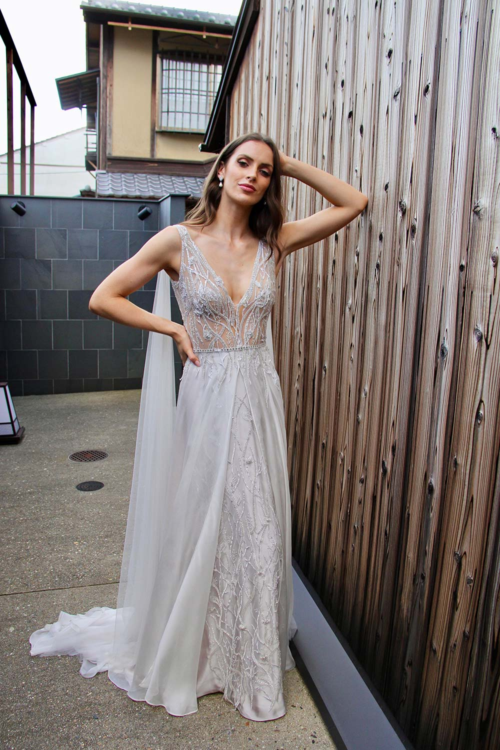 Female model wearing Vinka Design An Oriental Affair Wedding Dress. On a Japanese street the front detail of a gown with a sheer, deep v-neckline bodice with swarovski diamante belt, tulle cape and silver silk chiffon skirt.