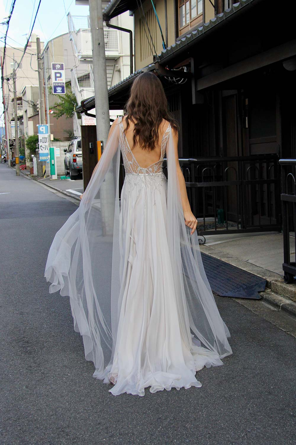 Female model wearing Vinka Design An Oriental Affair Wedding Dress. On a Japanese street the back detail of a gown with a sheer, deep v-neckline bodice with swarovski diamante belt, tulle cape and silver silk chiffon skirt.