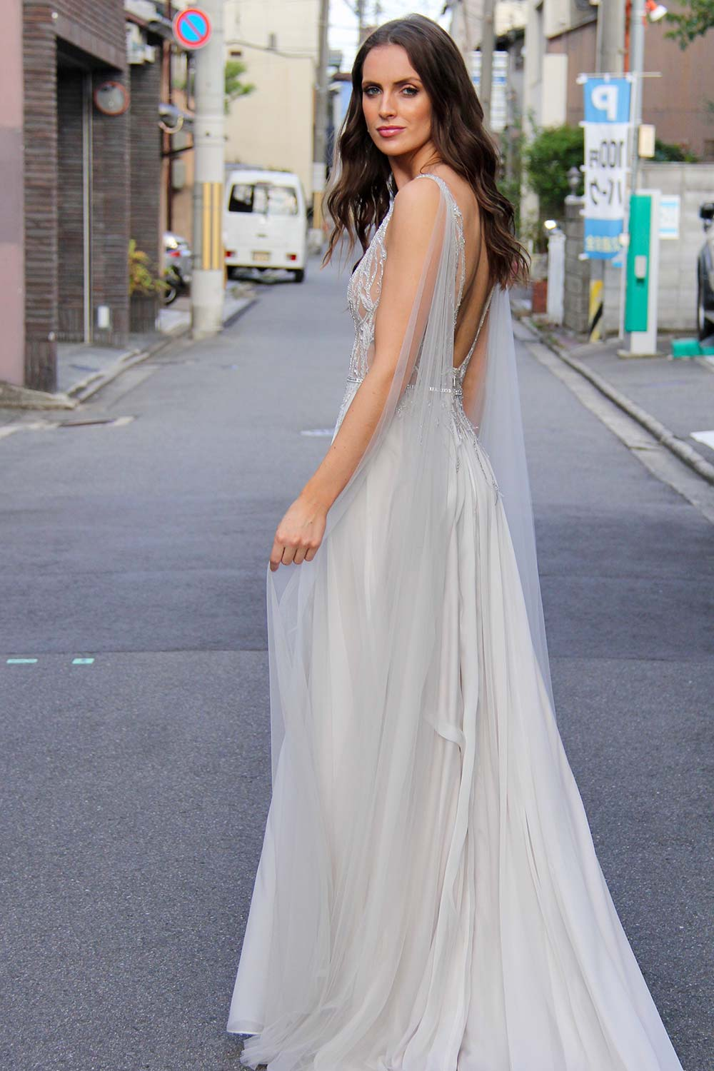Female model wearing Vinka Design An Oriental Affair Wedding Dress. On a Japanese street the side detail of a gown with a sheer, deep v-neckline bodice with swarovski diamante belt, tulle cape and silver silk chiffon skirt.
