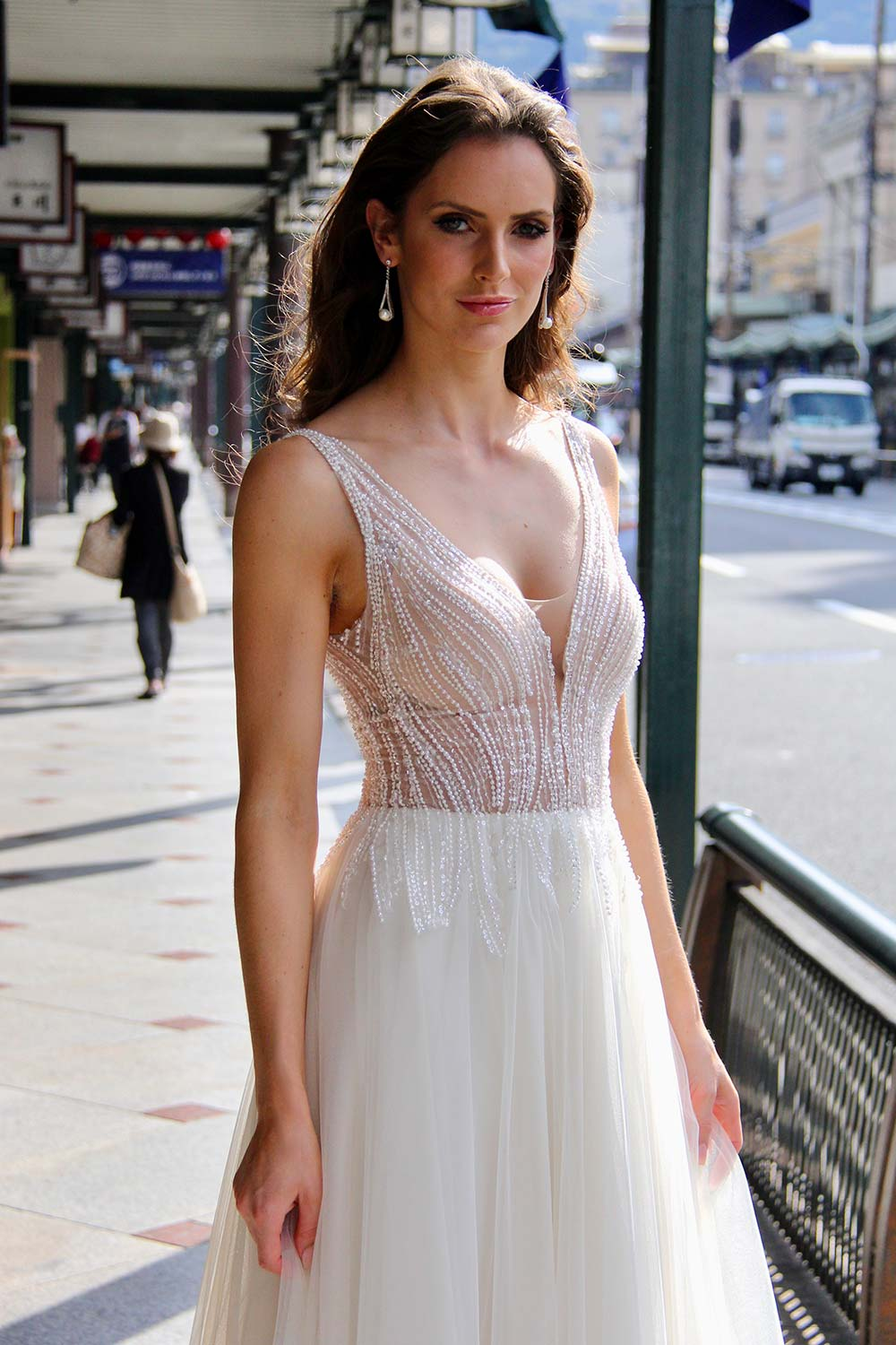 Female model wearing Vinka Design An Oriental Affair Wedding Dress. On a Japanese street the front detail of a gown with a hand-beaded, nude-based, semi sheer bodice with a deep v-neckline and low back with a tulle skirt.
