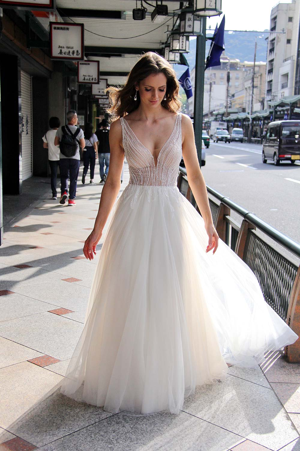 Female model wearing Vinka Design An Oriental Affair Wedding Dress. On a Japanese street the back detail of a gown with a hand-beaded, nude-based, semi sheer bodice with a deep v-neckline and low back with a tulle skirt.