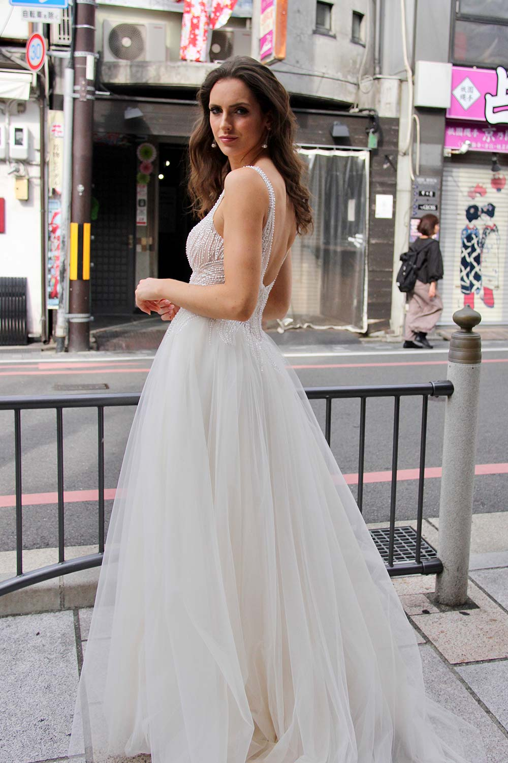Female model wearing Vinka Design An Oriental Affair Wedding Dress. On a Japanese street the side detail of a gown with a hand-beaded, nude-based, semi sheer bodice with a deep v-neckline and low back with a tulle skirt.