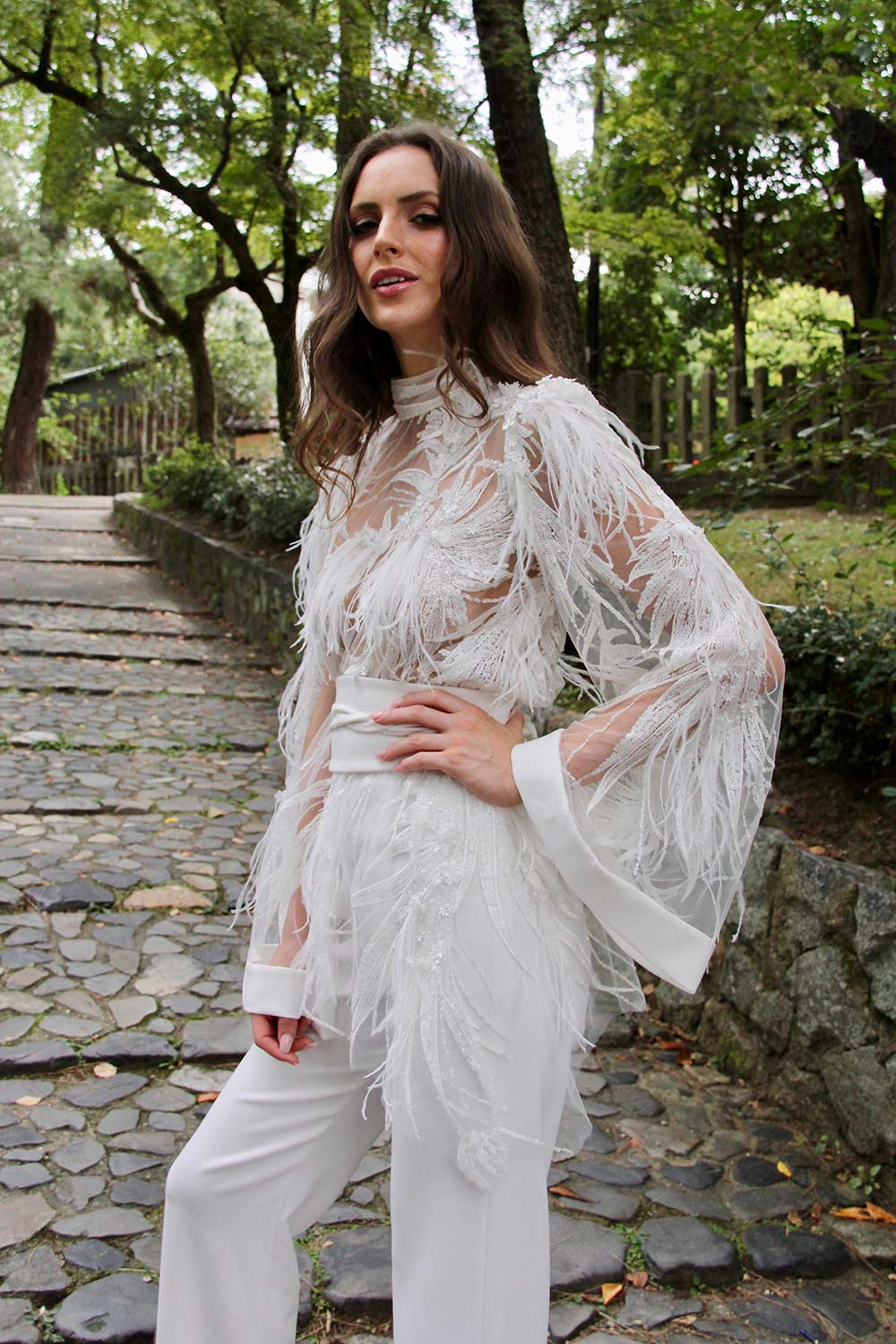 Female model wearing Vinka Design An Oriental Affair Wedding Dress. On stairs of a Japanese temple the front detail of gown with a bodice made with a dimensional beaded lace adorned with sequins and feathers and fitted trousers