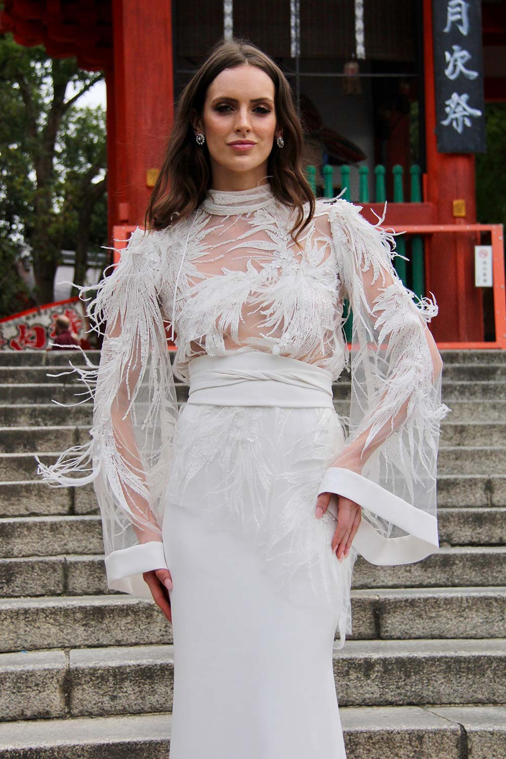 Female model wearing Vinka Design An Oriental Affair Wedding Dress. On stairs of a Japanese temple the front detail of gown with a bodice made with a dimensional beaded lace adorned with sequins and feathers and a fitted and flared skirt.