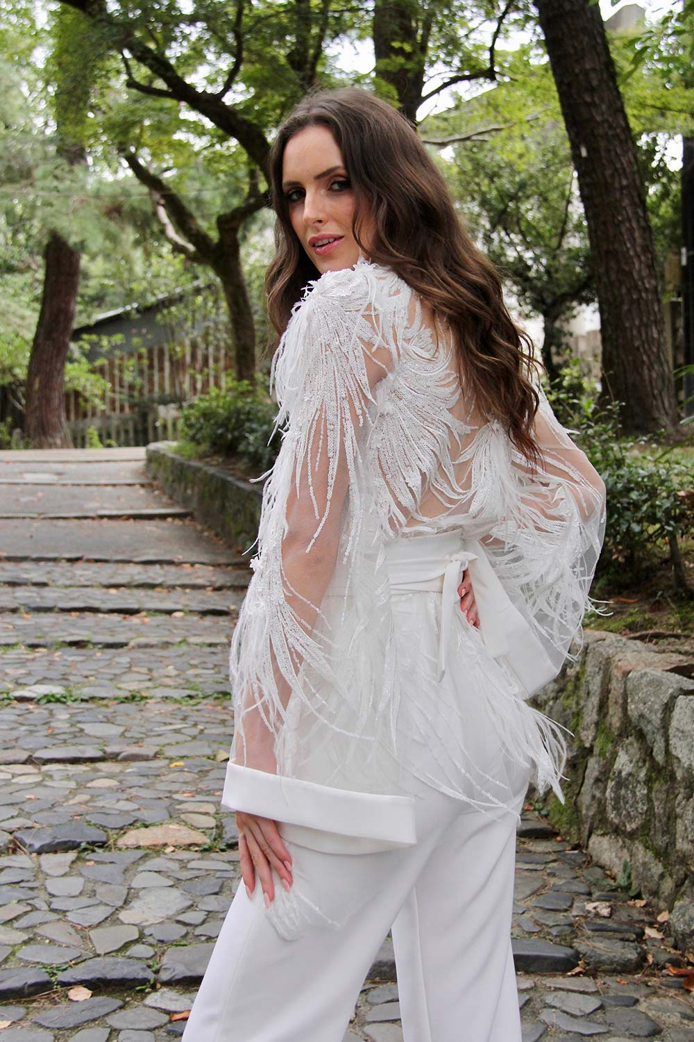 Female model wearing Vinka Design An Oriental Affair Wedding Dress. On stairs of a Japanese temple the back detail of gown with a bodice made with a dimensional beaded lace adorned with sequins and feathers and fitted trousers
